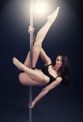 beautiful young woman performing on pole
