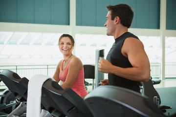 Gym: Friends Talking While Running On Treadmill