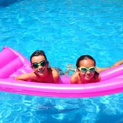 Niños en piscina sobre colchoneta fucsia