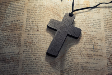 wooden cross on a old bible