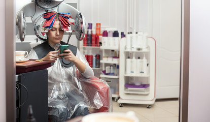 Young woman having her hair processed during hair colouring