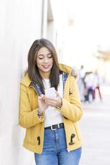 Smiling beautiful latin woman using smart phone in the street.