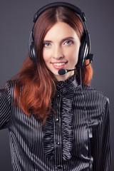 beautiful business woman with headphones against dark grey backg