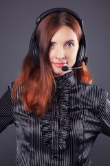 beautiful business woman with headphones against dark grey backg