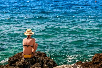 Woman read a books in wild beach near in Pula