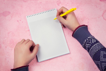 male hand making notes in blank notebook against pink background