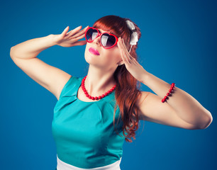 beautiful pin-up girl posing with red heart-shaped sunglasses ag