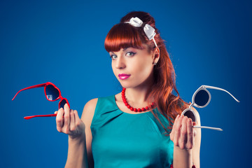 beautiful pin-up girl posing with two pairs of sunglasses agains