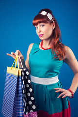 beautiful pin-up girl posing with shopping bags against blue bac