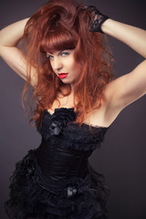 gothic redhead woman in sexy black satin corset against dark gre
