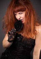 gothic redhead woman in sexy black satin corset against dark gre