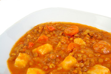 Brown cooked lentils with sausage, carrot and potato.