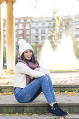 Beautiful smiling woman with scarf and cap sitting on stairs.