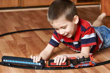 Happy little boy playing with railway
