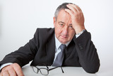 Businessman sitting at desk, holding his hand to his head