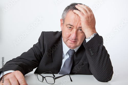 canvas print picture Businessman sitting at desk, holding his hand to his head