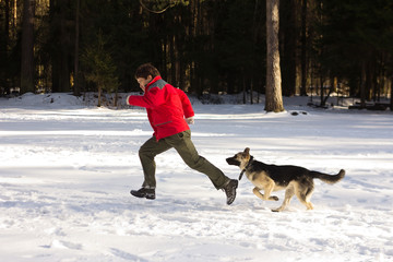 man playing with the dog in snow