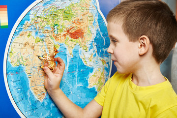 Little boy with toy giraffe shows Africa on world map