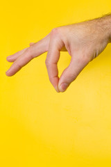 Male hand holding your product on yellow background