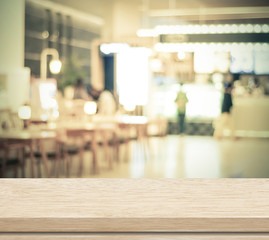 Empty wood table and blurred cafe with bokeh light background
