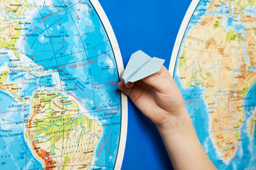 Small paper airplane on intercontinental flight to world map