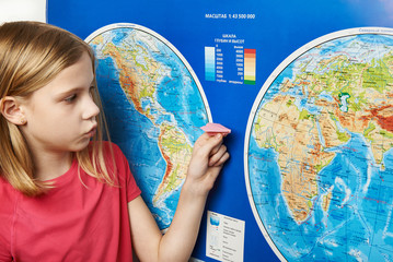 Girl holding paper plane on world map