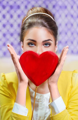 Beautiful woman holding a red heart