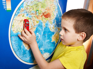 Little boy with toy car near world map