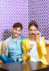 Cute young couple sitting at the table having fun