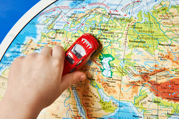 Child's hand with toy car on map of Eurasia