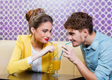 Cute young couple sitting at the table sharing a drink