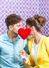 Cute young couple sitting at the table kissing behind a heart