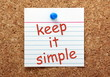 Keep It Simple reminder note on a cork notice board