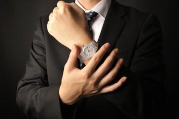 アナログの腕時計をしているブラックスーツの男性