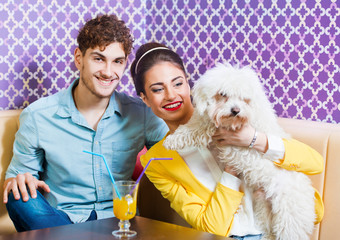 Cute young couple sitting at the table with a puppy