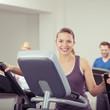 lachende junge frau trainiert im fitnessraum