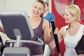 frau trainiert mit einer trainerin im fitness-studio