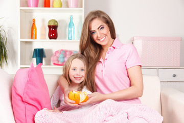 Happy mother and child eating fruit