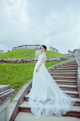 Beautiful woman in vintage wedding dress stay on stairs