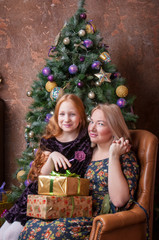 Mother and daughter sitting at the Christmas tree with gifts