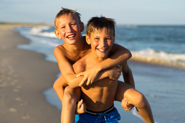 Portrait of two happy kids playing on the beach on summer vacati