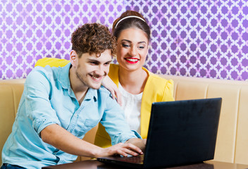 Cute young couple sitting at the table with laptop