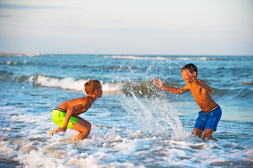 Two boys playing at the beach with water. Big splashes