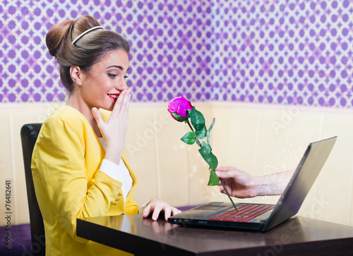 Man offering a rose to a beautiful woman over laptop screen - 76482641