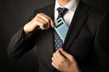 水色のデジタル計算機を手にしているスーツのビジネスマン男性