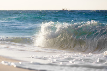 Waves on the beach of a tropical sea on sunset