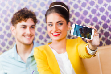Woman and man sitting at cafe, taking a selfie