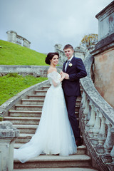 Beautiful bride and groom stay on stairs among mountain landscap