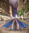 A row of blue bicycles on New York street at night