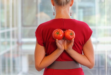fit business woman with tomatoes as a healhy snack